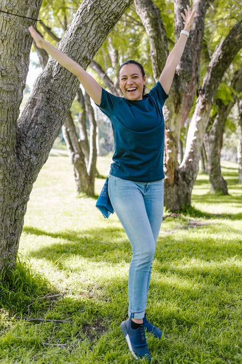 Woman in Blue Shirt Standing Beside A Tree With Arms Raised