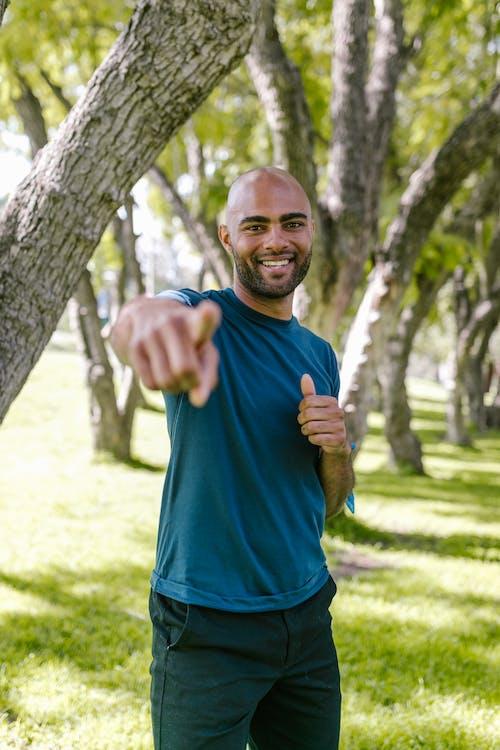 Man in Blue Crew Neck T-shirt Standing Beside Brown Tree