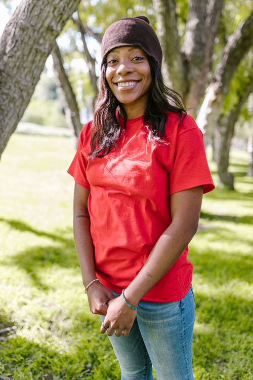 Smiling Woman in Red Shirt and Blue Denim Jeans Standing on Green Grass