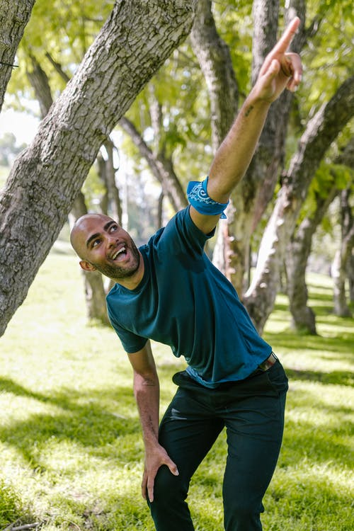 Man in Green Crew Neck T-shirt and Black Pants Standing Beside Brown Tree