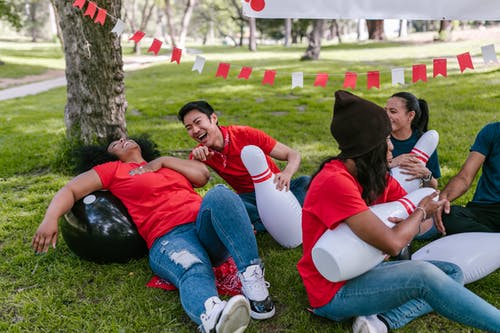 Group of People Sitting On Grass With Man And Woman Laughing Hard