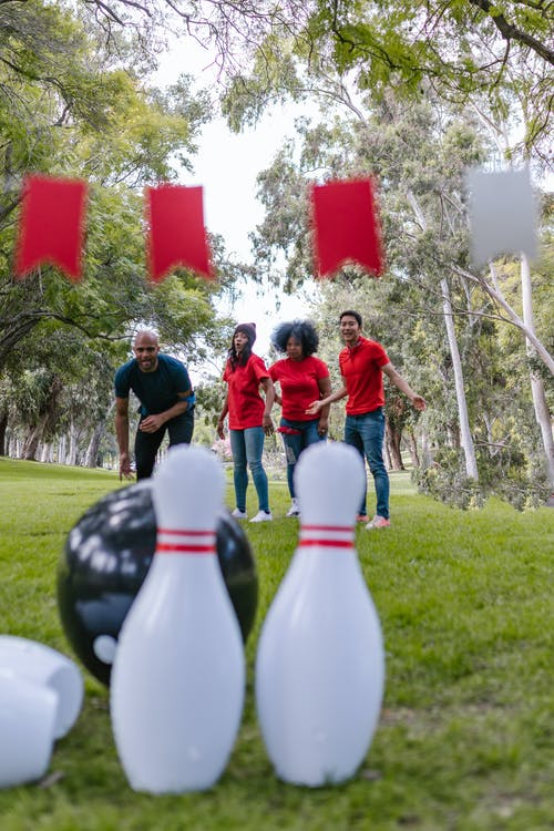 Group of People Playing Bowling On Grass