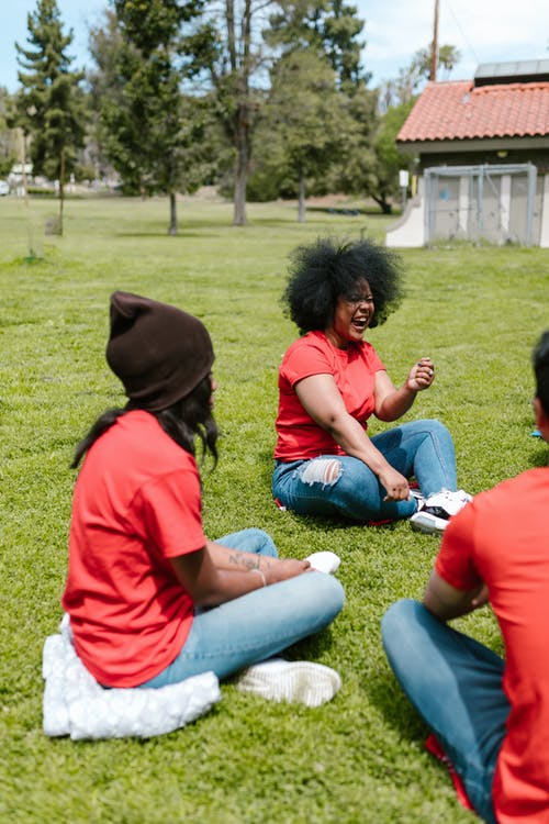 People in Red T-shirts Sitting on Green Grass