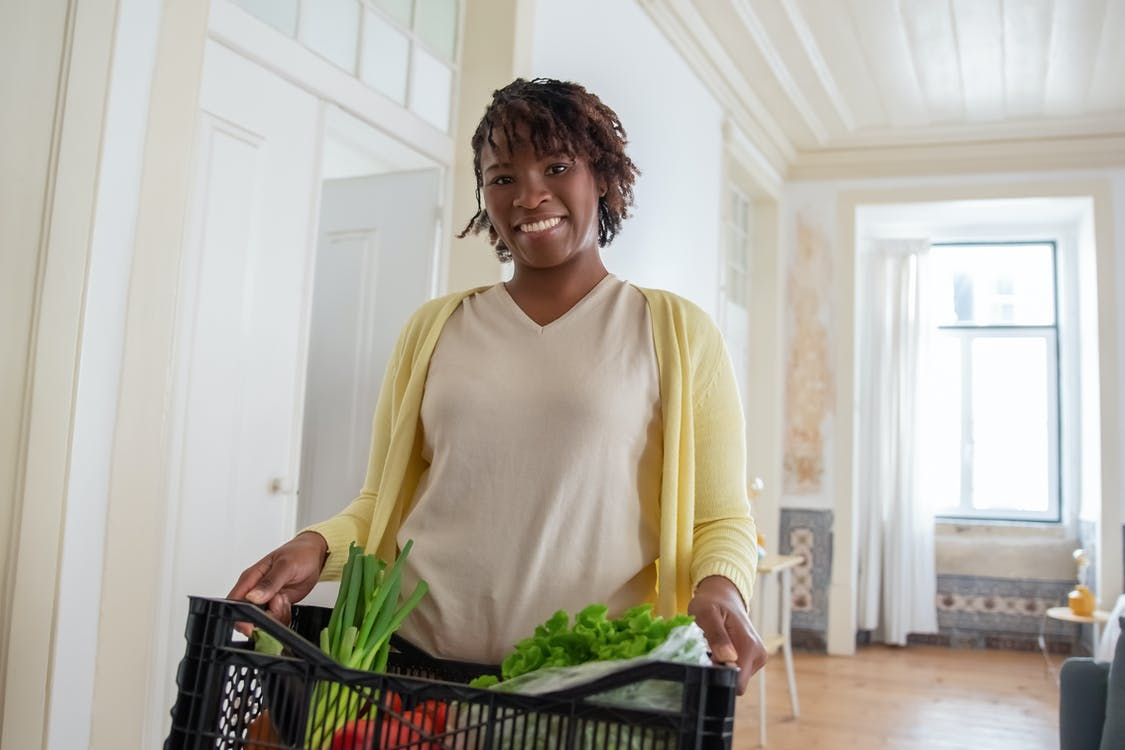 A Smiling Woman Holding a Plastic Crate of Vegetables