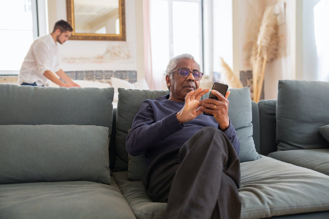 Man in Black Long Sleeve Shirt Sitting on Gray Couch