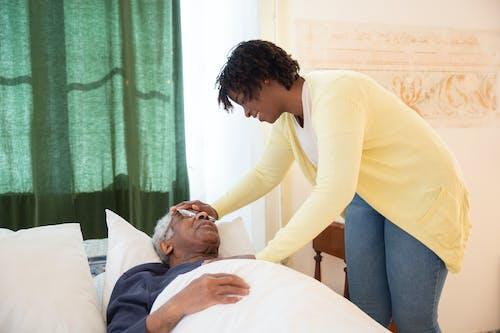 Woman Touching Elderly Mans Head
