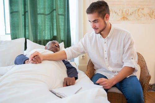 Man in White Button Up Shirt Sitting Beside Elderly Man in Bed