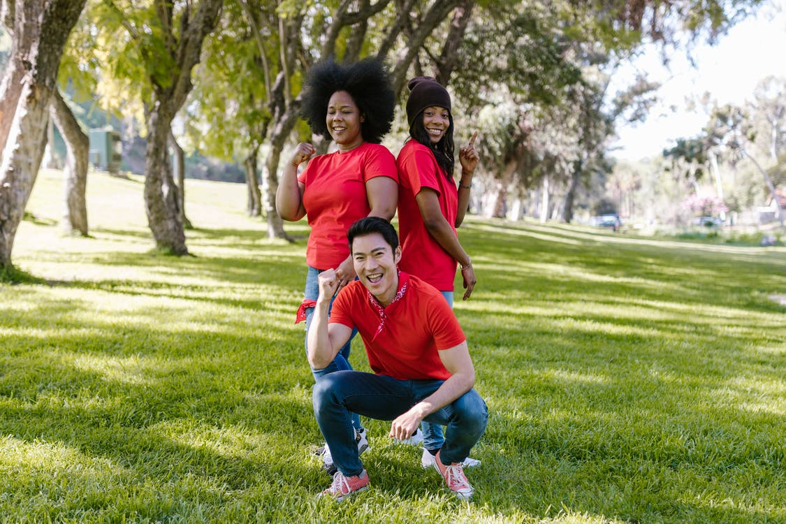 Man in Red Crew Neck T-shirt Sitting Beside Two Women Standing