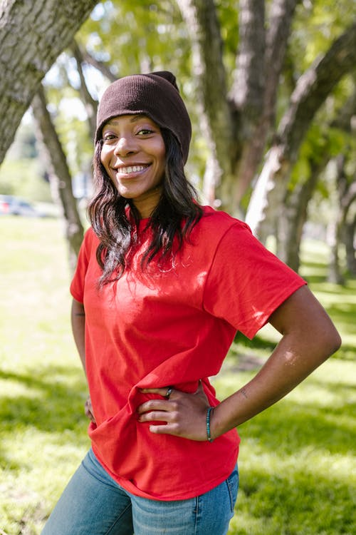 Smiling Woman in Red Crew Neck Shirt and Black Knit Cap