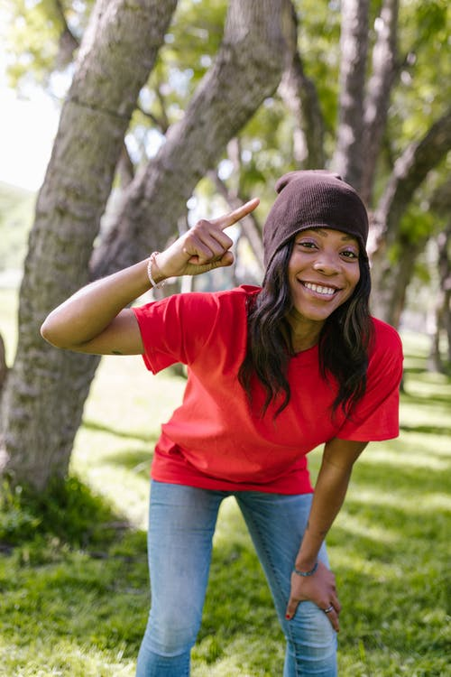 Smiling Woman in Red T-shirt and Blue Denim Jeans Holding Brown Stick