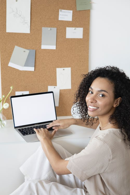 Woman in White Long Sleeve Shirt Holding Macbook Pro