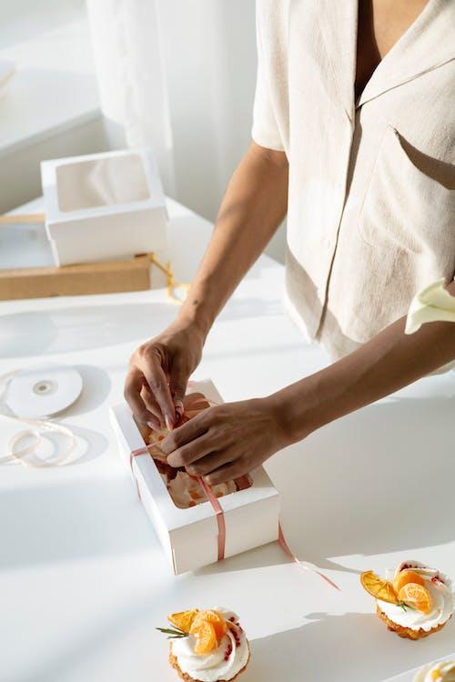 Person Tying the Ribbon on Cardboard Box