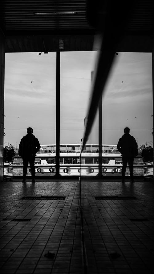 Monochrome Photo of Person Standing on Glass Wall