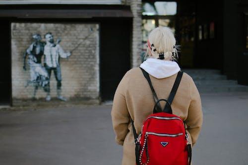 Woman in Beige Coat With Red Backpack Walking on Sidewalk