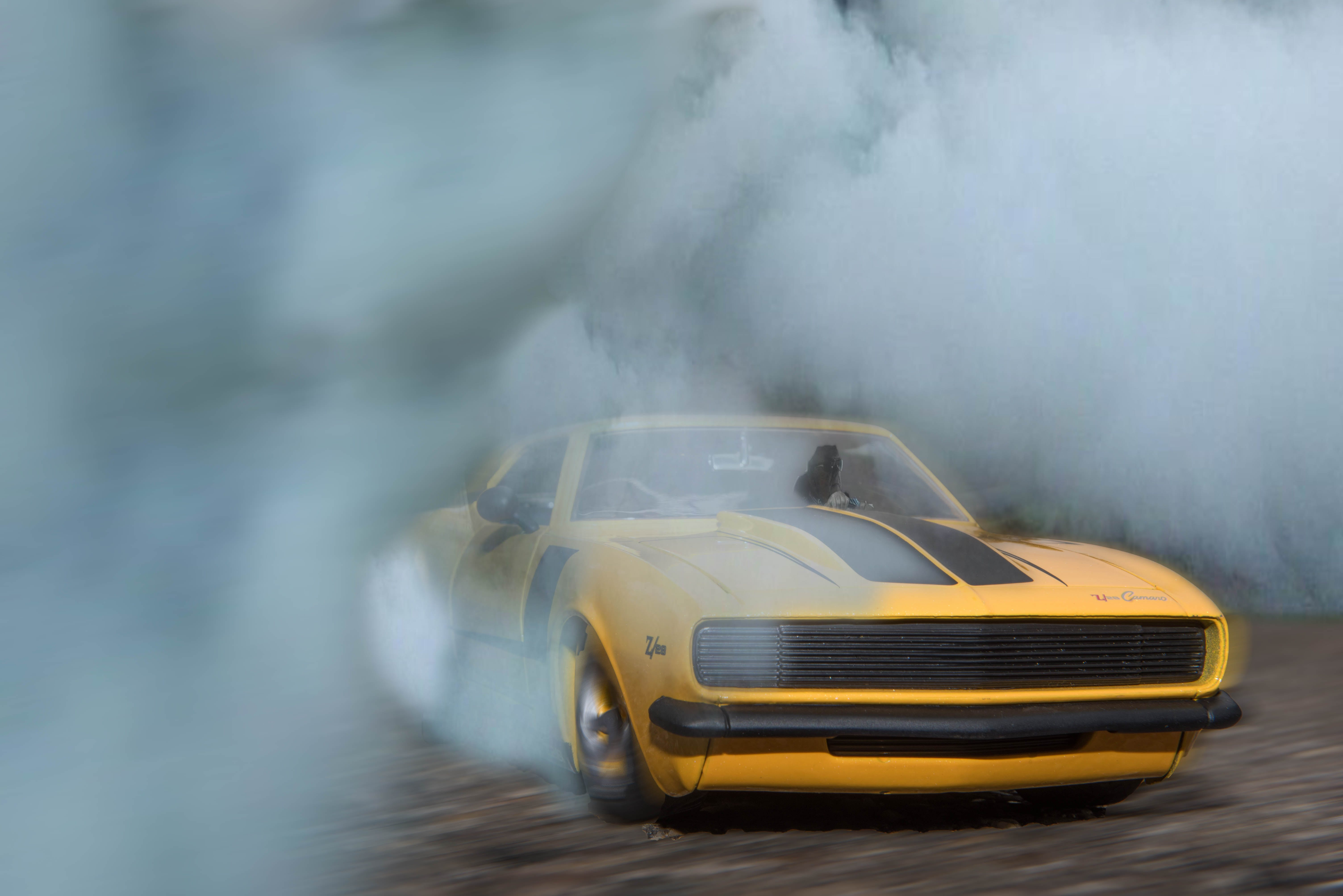 Classic Yellow And Black Sports Car Drifting On Road With Smoke