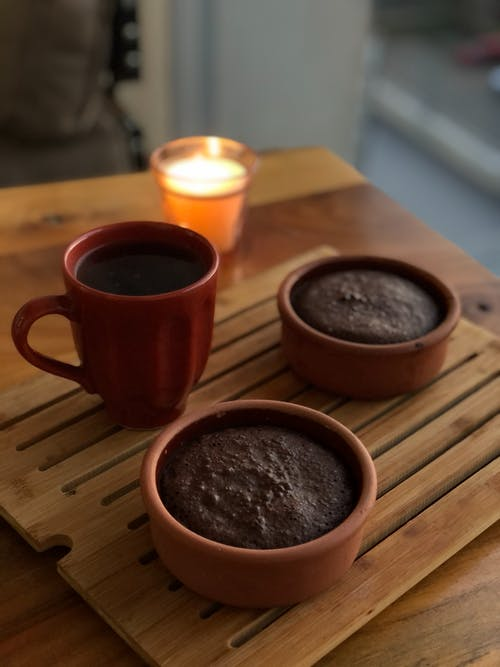 Red Ceramic Mug and Brown Puddings on Wooden Board