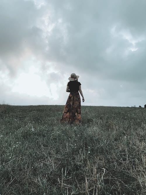 Unrecognizable woman walking on grassy meadow