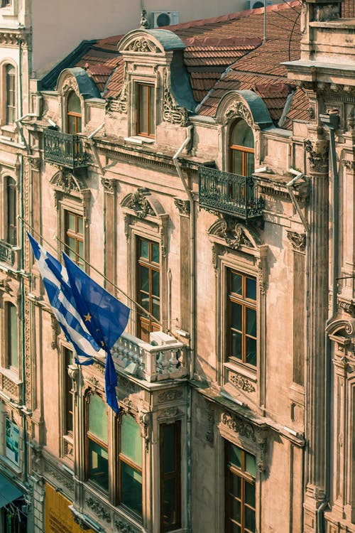 Waving flags of Greece and European union on shabby embassy building with balcony and windows on sunny street in city