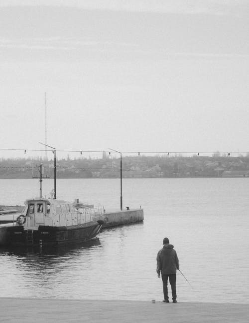 Black and white back view of distant unrecognizable male with fishing rod standing on embankment near rippling river with moored motorized boat on dock