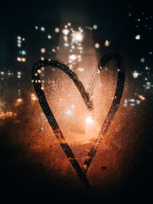 Heart drawn on glass of wet window with view of light of buildings on city street at night