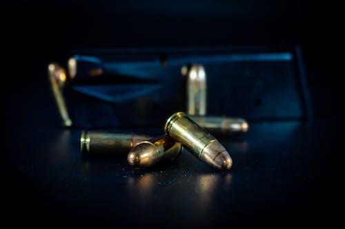 Gold Bullets on Black Surface