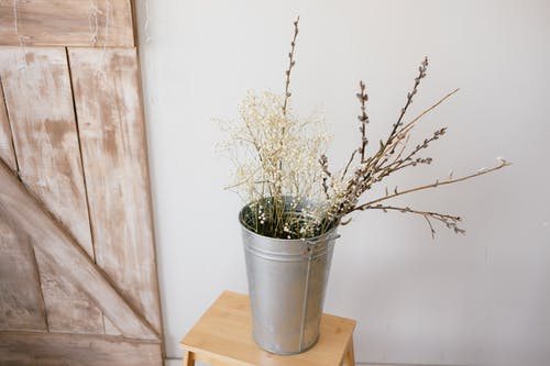 Metal Bucket with Flowers on Wooden Chair