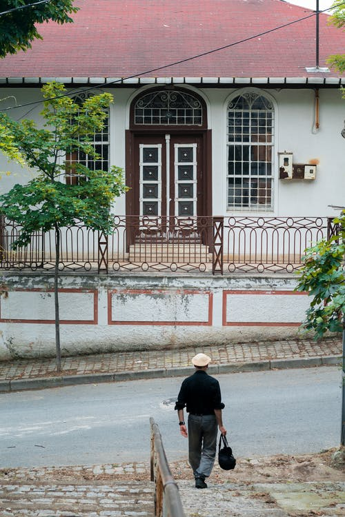 Back view of distant anonymous male in hat strolling on street with asphalt road and residential house with metal fence