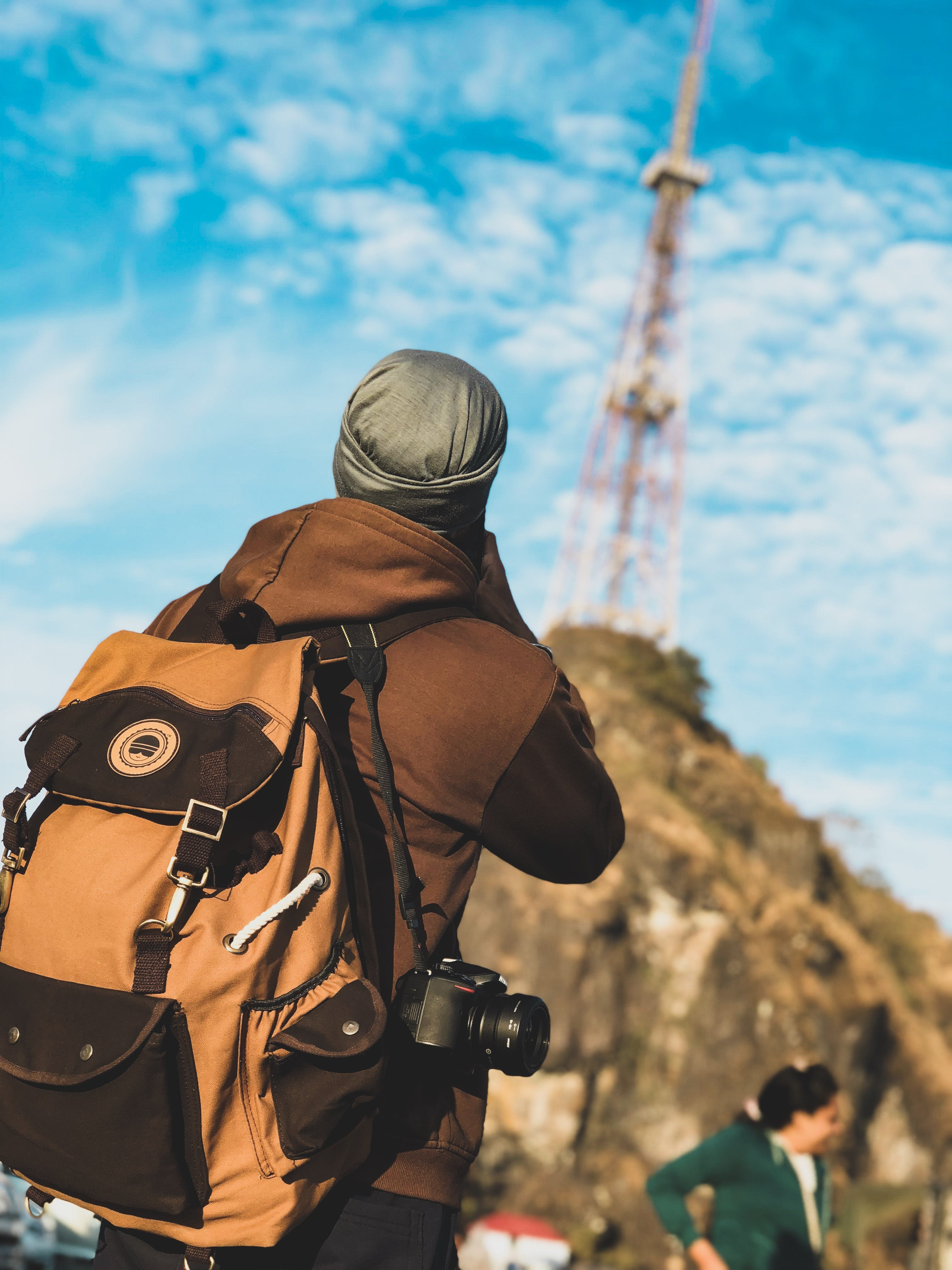 Focus Photography of Person Wearing Brown and Black Jacket With Brown and Black Backpack