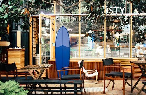 Blue Surfboard Leaning on Desk