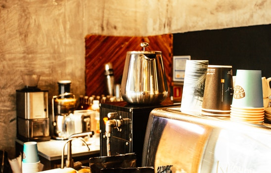 Stainless Steel Coffee Pot and Disposable Cups on Top of Counter