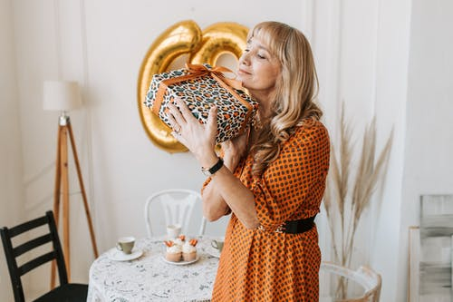 Woman in Black and Orange Dress Holding Brown and Black Cake
