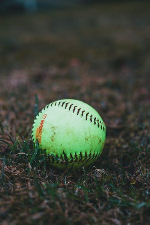 Close-Up Shot of a Green Baseball on a Grassy Field