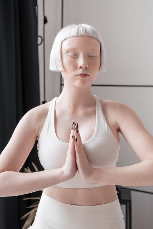 Photo of a Woman with Short Hair Meditating with Her Eyes Closed