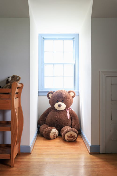 Brown Bear Plush Toy on Brown Wooden Chair
