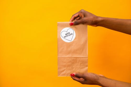 Kostnadsfri bild av förpackning, gul bakgrund, håller