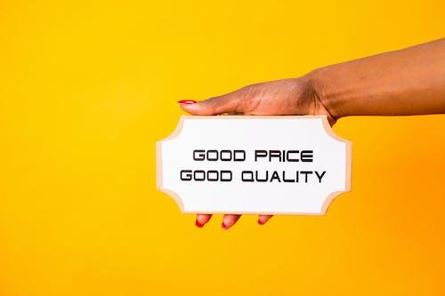 Kostnadsfri bild av bra pris bra kvalitet, gul bakgrund, håller