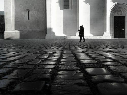 Man and Woman Walking on Empty Street