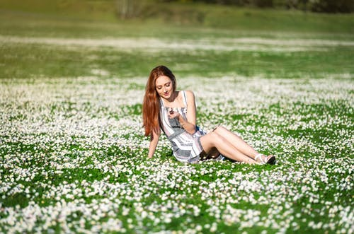 Woman in White Tank Top and Blue Denim Shorts Sitting on Green Grass Field