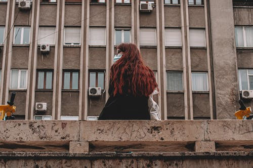 Back View of a Woman with Red Hair Sitting on a Concrete Bench