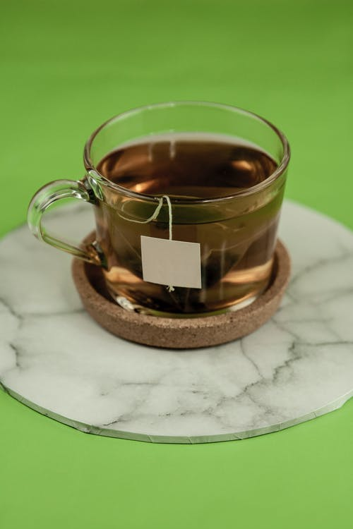Black tea bag in glass cup placed on ceramic cup holder with marble surface on light green table