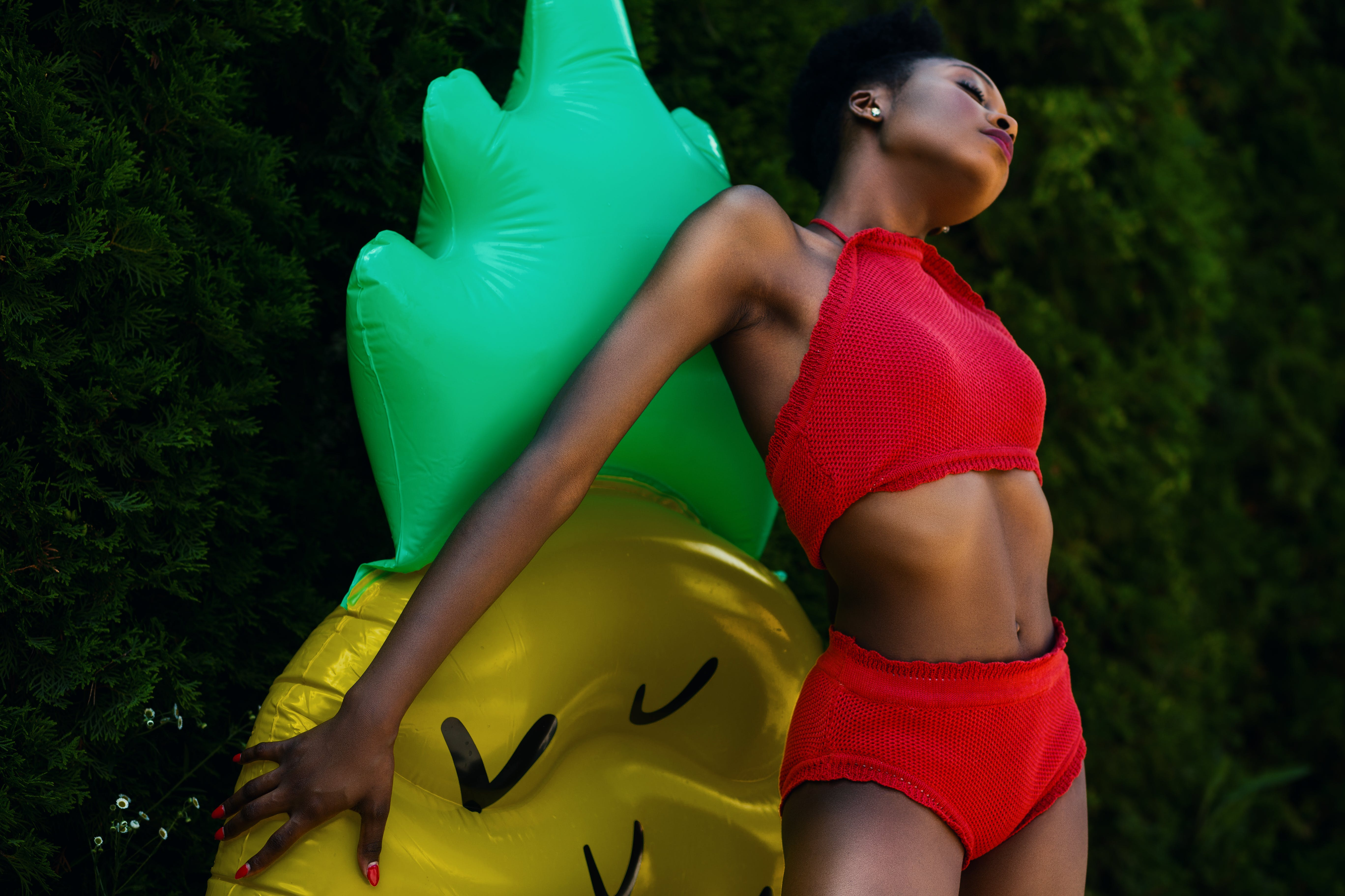 Woman Wearing Red Top and Bottoms Leaning on Yellow and Green Inflatable Standee