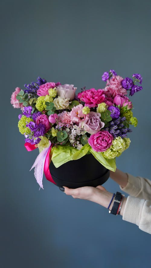 Crop anonymous female florist demonstrating elegant bouquet of fresh colorful assorted flowers against gray background
