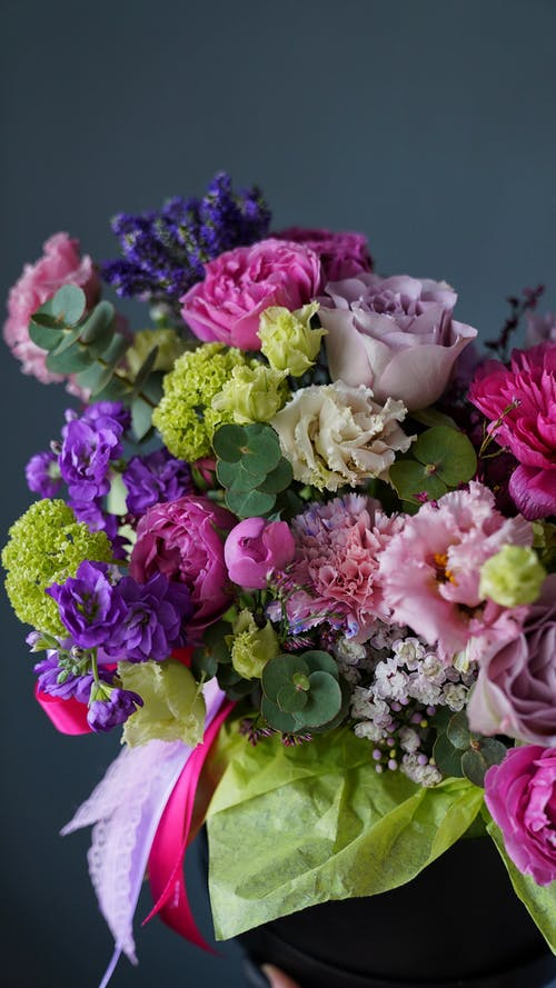 Bunch of fresh colorful roses arranged with assorted gentle flowers wrapped in pink and green papers against gray background