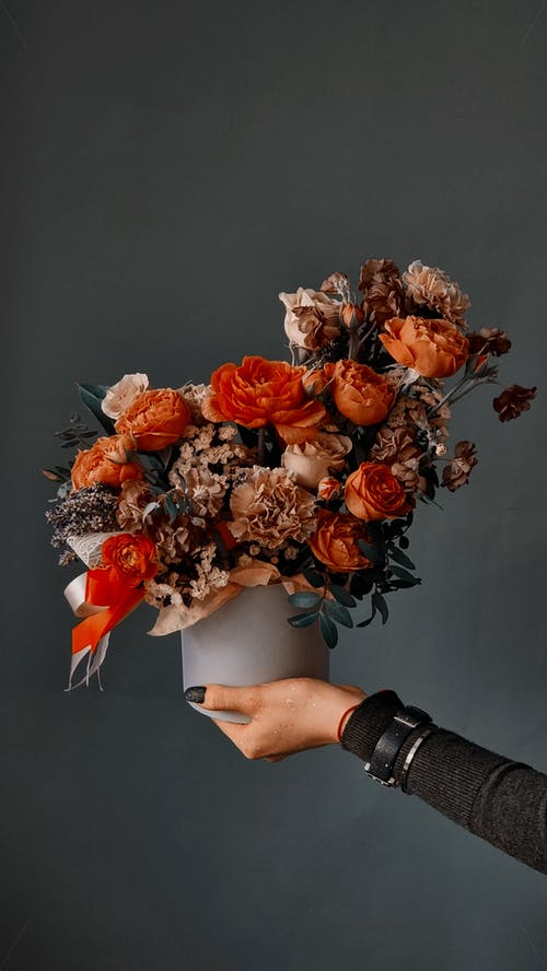 Unrecognizable florist showing bouquet of tender cultivated roses in studio