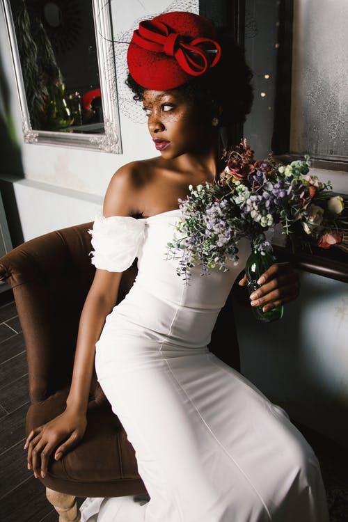 Woman Wearing White Off-shoulder Bodycon Dress Holding Flower Arrangement in Vase