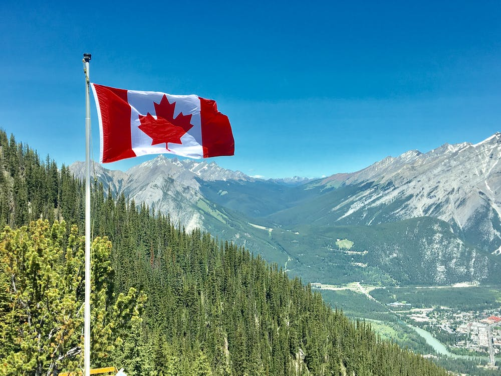 Canada Flag With Mountain Range View