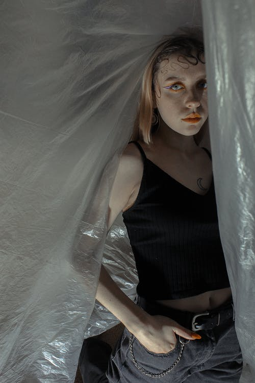 Confident female with creative makeup and hairstyle standing with hand in pocket among transparent stretch plastic wrap and looking at camera