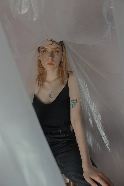 Pensive female with stylish makeup and tattoos in black clothes sitting among transparent plastic wrap and looking at camera