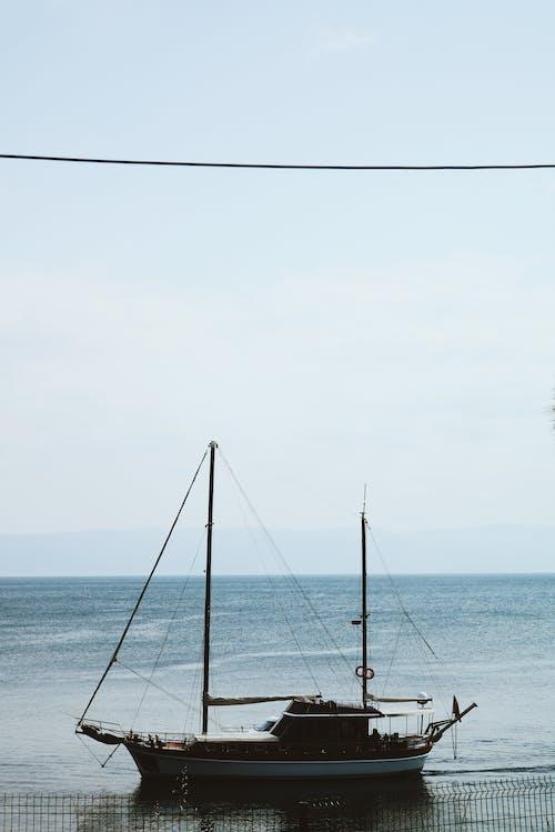 Sailboat on calm sea shore at sunlight