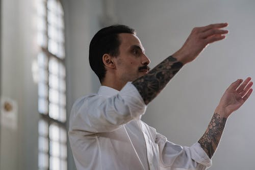 Man in White Dress Shirt With Arm Tattoo